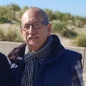 A photo of John, AKA Attila the Budgie, wearing a scarf and glasses
